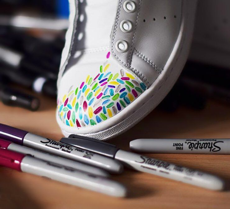 Assorted Sharpie markers next to decorated sneaker