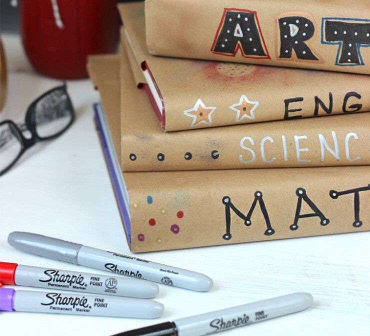 Assorted Sharpie markers next to text books